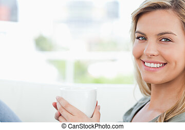 Woman smiling, looking forward and holding up a mug in hands...
