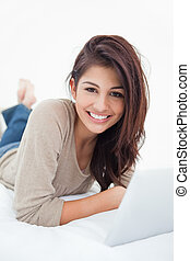 A smiling woman looks in front of her as she smiles, with her tablet on the bed with her.