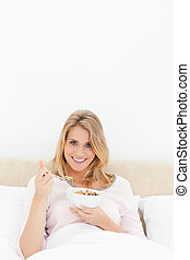 A vertical shot of a woman in bed, with a bowl and spoon of cereal in her hands as she looks forward and smiles.