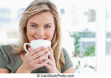 Woman looking forward, smiling with a mug up to near her...