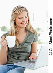 A woman looking slightly sideways, as she uses her laptop...