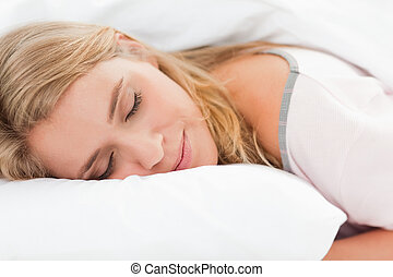 Woman lying in bed, her head on a pillow and eyes closed