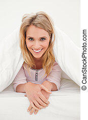 Woman in bed under a quilt, looking forward and smiling