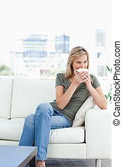A woman sitting on the couch, with a mug up to her nose, and...