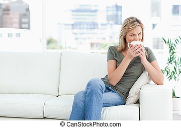 A woman sitting on the couch with a mug up to her nose, legs...