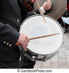 By tapping the drum - musician of orchestra playing the drum...