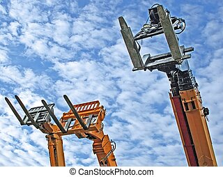 three fork-lift trucks, pointing towards the sky, waiting...