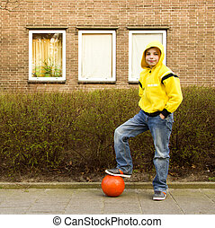 Cute teenage boy in a yellow hoodie with an orange ball