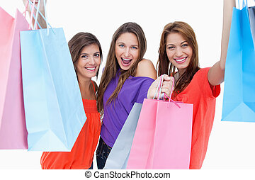 Happy teenagers raising their arms while holding their purchase bags