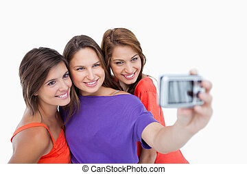 Three beautiful teenagers being photographed while standing...