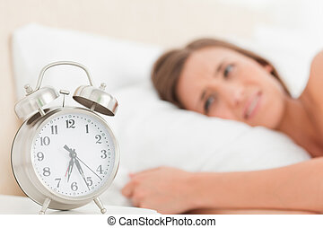 Woman in bed with her alarm clock beside her showing the time
