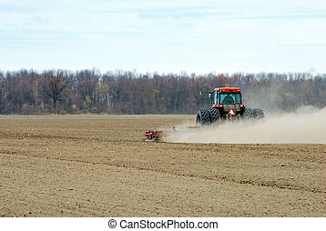 Spring ploughing a dry farm field early morning