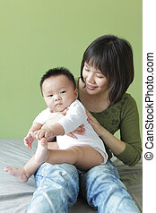 Mother and her baby sit on the bed, model are asian family