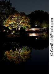 Japanese garden at night with a small hut on lakeside -...