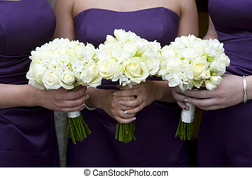 bridesmaids with flowers - three bridesmaids holding wedding...