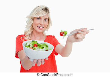 Young blonde woman holding a bowl of fresh salad