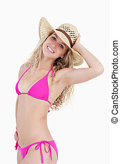 Smiling blonde teenager holding her hat
