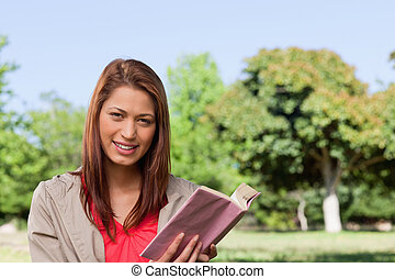 Woman grinning while looking straight ahead with a book in her hands in a sunny grassland area
