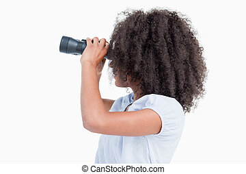 Side view of a young woman looking through binoculars