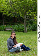 Smiling teenage girl doing her homework while sitting on the...