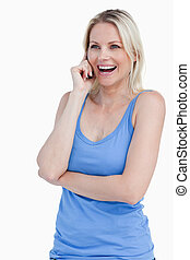 Blonde woman using a cellphone while laughing against a...