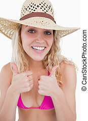 Smiling young attractive woman putting her two thumbs up