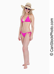 Woman wearing pink swimsuit with a hat and sunglasses while standing upright