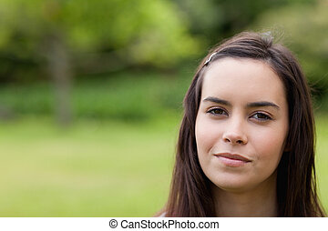 Young calm woman standing upright in a parkland