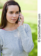 Serious young woman calling with her cellphone while standing upright in a park