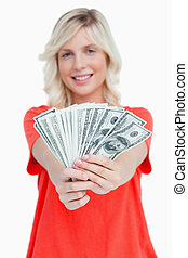 A fan of dollar notes held by a smiling attractive woman...