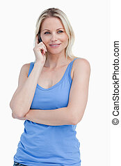 Blonde woman using a cellphone while standing with her arms...