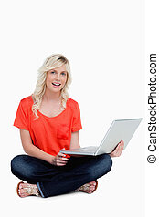 Young woman sitting cross-legged holding her laptop