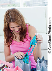 Young woman looking at her new blue swimsuit - Young woman...