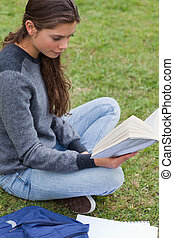 Relaxed young girl reading a book while sitting on the grass