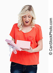 Young blonde woman showing her surprise while opening a present