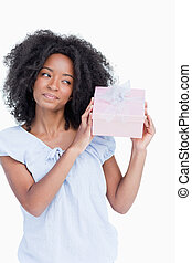 Young woman shaking her gift in order to guess what it is -...