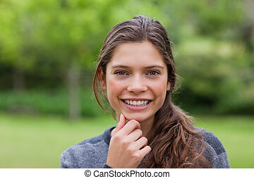 Smiling young adult placing her hand on her chin while standing up in the countryside
