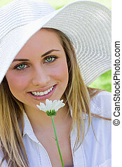 Young pretty blonde girl wearing a hat while holding a white...