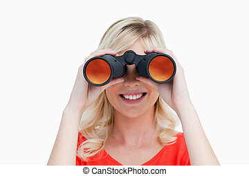 Blonde woman looking through binoculars against a white...