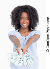 A fan of dollar notes held by a smiling woman with curly...