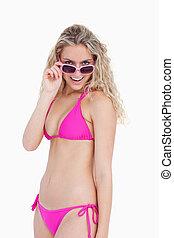 Smiling teenager in beachwear looking over her sunglasses