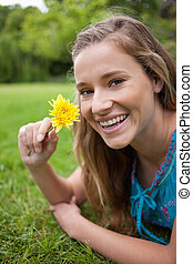 Smiling teenager holding a beautiful flower while lying on...