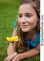 Young thoughtful girl lying on the grass while holding a...
