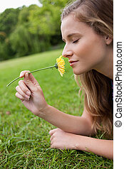Young relaxed girl closing her eyes while smelling a yellow...