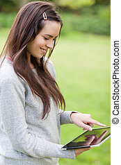 Young happy girl using her tablet pc while standing upright...