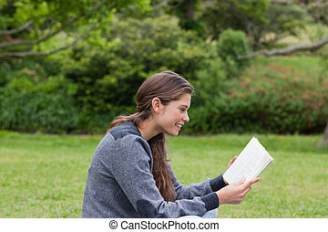 Side view of a young girl showing a great smile while reading a book on the grass