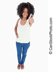 Young smiling woman putting her thumbs up and a hand on hip