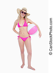 Smiling teenager in beachwear holding a beach ball