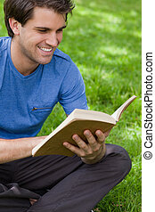 Young smiling man reading a book while siting on the grass -...