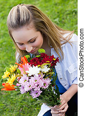 Young attractive girl smelling a bunch of flower while...
